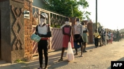 FILE - People line up for a food handout amid the coronavirus pandemic, in Chitungwiza, Zimbabwe, May 5, 2020.