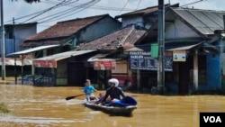 Warga memanfaatkan perahu sebagai alat transportasi saat banjir melanda Kabupaten Bandung, Jawa Barat (VOA/Teja Wulan).