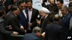 Presiden Iran Hassan Rouhani, tengah, saat disambut oleh para anggota DPR di parlemen untuk menyampaikan draft anggaran negara Iran tahun depan dan rencana pembangunan di Teheran, 17 Januari 2016.