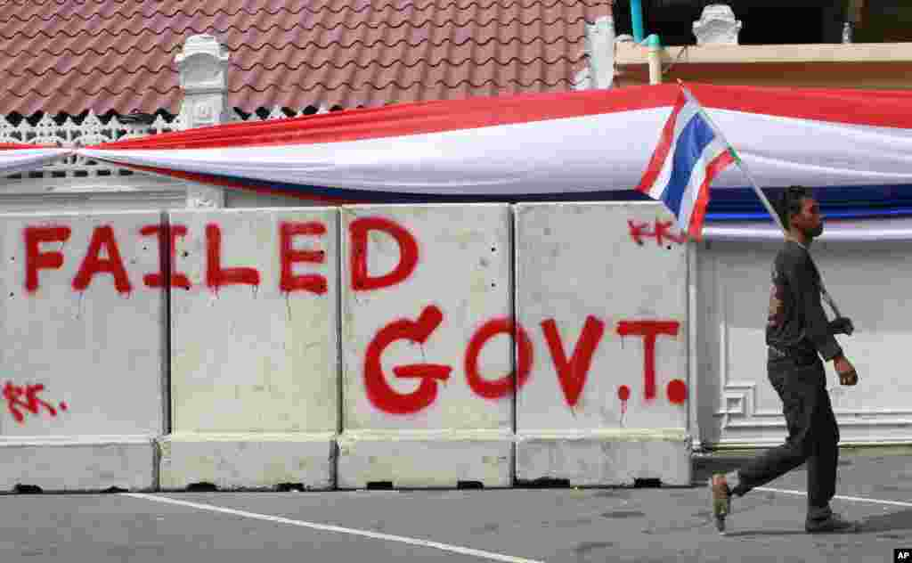 "A protester with a Thai national flag walks past concrete barriers sprayed with ""Failed Government"" outside the fence around Government House, wrapped by a long banner in the colors of the national flag in Bangkok, Dec. 13, 2013."