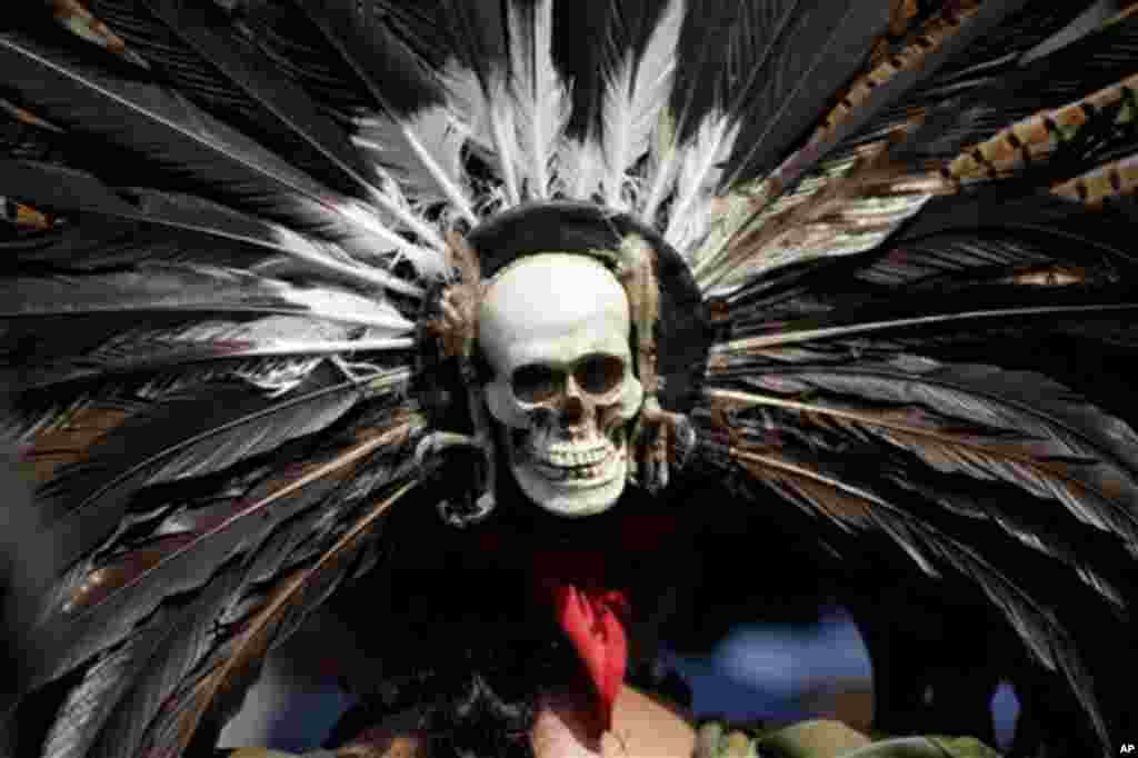 A mask in the likeness of a human skull adorns the back of a head piece worn by an Aztec dancer during a demonstration outside Mexico City's Legislative Assembly, Tuesday Nov. 8, 2011. The city legislature's Indigenous Commission is proposing a law that