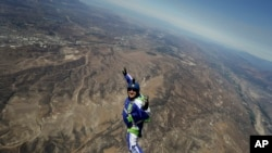 In this Monday, July 25, 2016 photo, skydiver Luke Aikins smiles as he jumps from a helicopter during his training in Simi Valley, California.