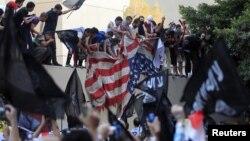 Para demonstran Mesir yang marah menurunkan bendera Amerika di Kedubes AS di Kairo dan merobek bendera itu, Selasa (11/9).