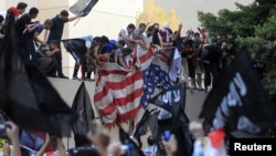 Protesters destroy an American flag pulled down from the U.S. embassy in Cairo, September 11, 2012.