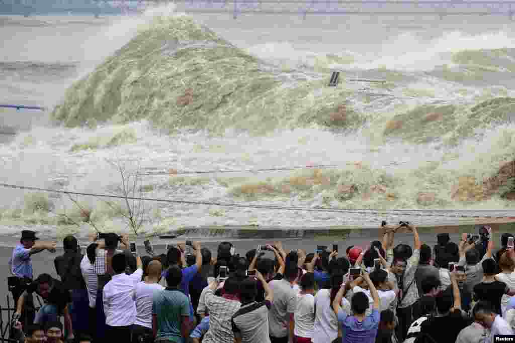 People take pictures as they watch waves caused by a tidal bore on the bank of the Qiantang River, in Hangzhou, Zhejiang province, China, Sept. 30, 2015.