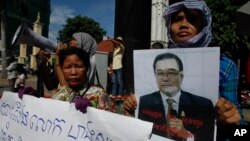 A Cambodian opposition party supporter, right, holds a portrait photo of an opposition senator Hong Sok Hour during a protest in front of the Phnom Penh Municipal Court, in Phnom Penh, Cambodia, Saturday, Aug. 15, 2015. Cambodian authorities arrested an opposition senator Saturday, two days after Prime Minister Hun Sen accused him of treason for comments posted on Facebook. A slogan reads: free senator Hong Sok Hour. (AP Photo/Heng Sinith)