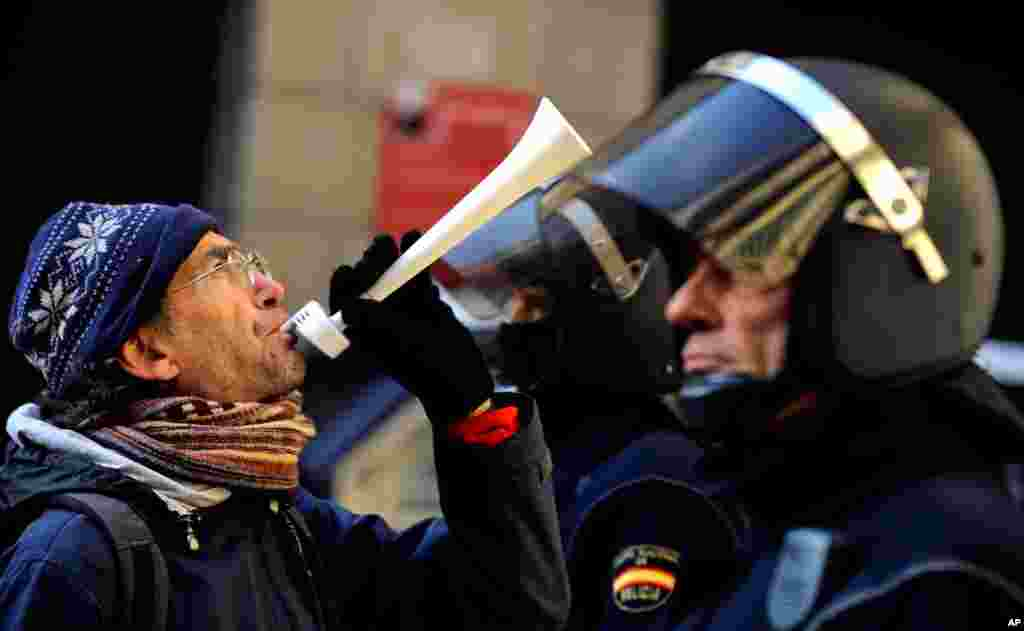 A demonstrator blows a horn in front of Spanish riot police during a strike against government austerity measures in Pamplona, Spain, November 14, 2012.