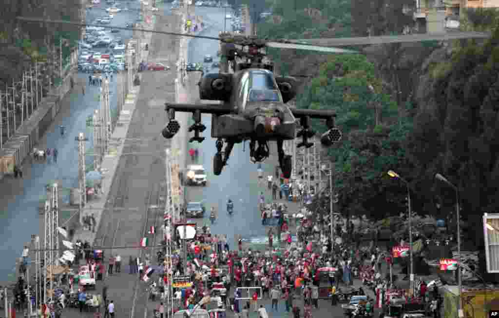A military attack helicopter flies near the presidential palace in Cairo, Egypt, Friday, July 5, 2013.
