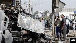 ບັນດາຄົນ ແລະເຈົ້າໜ້າທີ່ກໍາລັງກວດເບິ່ງ ສະຖານທີ່ເກີດລະເບີດຢູ່ໃນລົດ ທີ່ ຄູ້ມ Karrada ໃນກຸງ Baghdad, Iraq ວັນທື່ 13, ເດືອນມິຖຸນາ 2012.