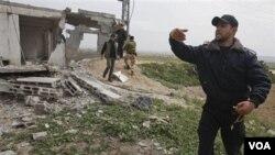 Beberapa anggota Hamas menginspeksi kerusakan setelah serangan udara Israel di Jalur Gaza, Sabtu (19/3).
