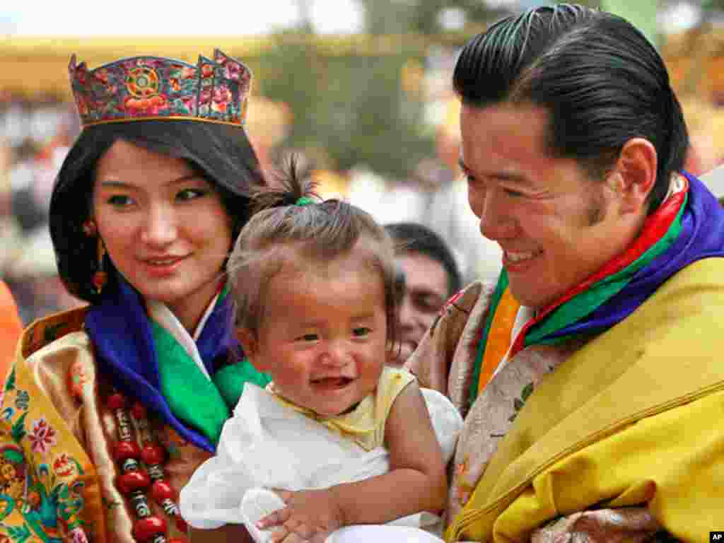 King Jigme Khesar Namgyal Wangchuck, right, holds a young child as he greets locals with Queen Jetsun Pema during a celebration after they were married at the Punakha Dzong in Punakha, Bhutan, Thursday, Oct. 13, 2011. The 31-year-old reformist monarch of