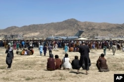 FILE - In this Aug. 16, 2021, file photo, hundreds of people gather near a U.S. Air Force C-17 transport plane at the perimeter of the international airport in Kabul, Afghanistan.