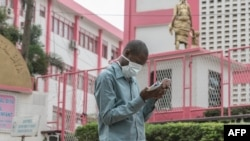 A man wears a mask while walking outside the entrance to the Yaounde General Hospital in Yaounde on March 6, 2020, as Cameroon has confirmed its first case of the COVID-19 virus.