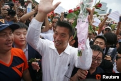Thanathorn Juangroongruangkit, leader of the Future Forward Party, greets his supporters as he arrives at a police station to hear a sedition complaint filed by the army in Bangkok, April 6, 2019.