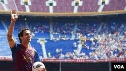 Pemain baru Barcelona Cesc Fabregas melambaikan tangan ketika diperkenalkan di stadion Camp Nou Barcelona, Senin (15/8).