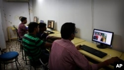 FILE - Indian youth use the internet at a cyber cafe in Allahabad, India. The hotline is a simple online form which the public, police, internet companies and victims can access in either Hindi or English.