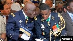 L'ancien chef d'état-major de l'armée ivoirienne, Philippe Mangou, à gauche, échange avec le commandant de la gendarmerie, le général Edward Tiape, à droite, d'une cérémonie au Plateau Abijan, 12 juillet 2011.