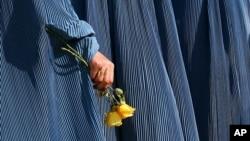 Một phụ nữ Afghanistan cầm hoa hồng vàng đánh dấu ngày Quốc tế phụ nữ tại thủ đô Kabul