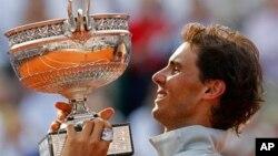 Petenis Spanyol, Rafael Nadal mengangkat trophy kejuaraan grand slam Perancis Terbuka yang ke-9, setelah menang atas Novak Djokovic di Roland Garros, Paris, Minggu (8/6).