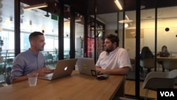 Brand strategist Phil Pallen (left) travels the world and works in the co-working spaces of a company called WeWork, seen here at a location in downtown Los Angeles. (M. O'Sullivan / VOA)