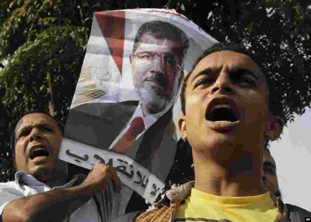 "A supporter of Egypt's ousted President Mohammed Morsi raises his poster during a protest in front of the supreme constitutional court in Cairo, Egypt, Nov. 4, 2013. The Arabic text reads, ""no to the coup."""
