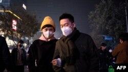 2018年11月26日一对夫妇戴口罩应对北京恶劣空气污染。