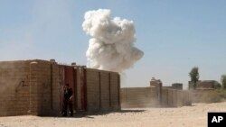 Asap mengepul pasca serangan bom bunuh diri di Lashkar Gah, Afghanistan hari Senin (10/10).