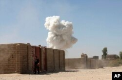 Smoke rises after a suicide attack in Lashkar Gah the capital of southern Helmand province of Afghanistan, Oct. 10, 2016.