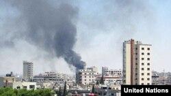 Khói bốc lên từ những tòa nhà bị pháo kích ở thành phố Homs
