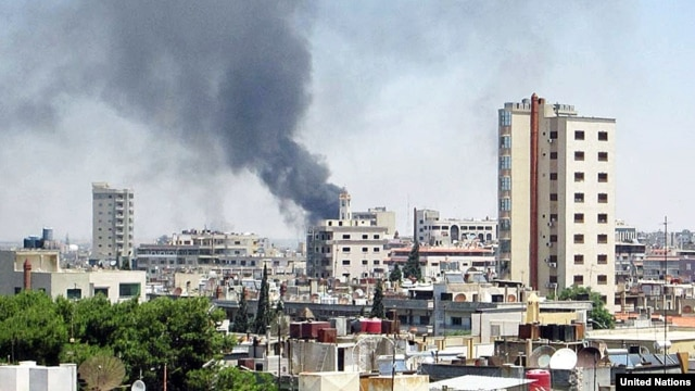 Smoke rises from buildings hit by shelling in Homs, Syria