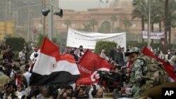 Sojoji suke kallon dubban masu zanga zanga da suka hallara a dandalin Tahrir.