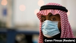 A security official wearing a protective mask keeps an eye on cars at a checkpoint between Jeddah and Mecca before the start of the annual Hajj pilgrimage November 21, 2009.