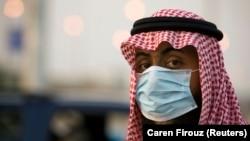 Seorang petugas di pos keamanan perbatasan antara Jeddah dan Mekah memakai masker. (Foto: Dok)