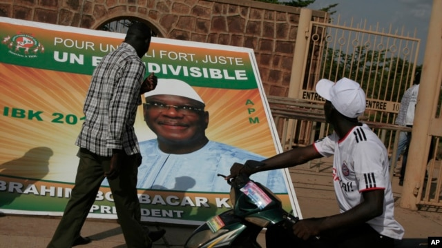 Passersby look at a poster supporting presidential candidate Ibrahim Boubacar Keita, with the slogan 'For a strong, just Mali, one and indivisible,' on the first day of campaigning, in Bamako, Mali, July 7, 2013.