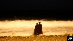 Dua perempuan Saudi menikmati pantai Laut Merah di Jeddah, Saudi Arabia di waktu malam (foto: ilustrasi).