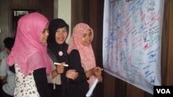 Penandatanganan petisi warga desak pemerintah wujudkan RUU perlindungan PRT mengisi kegiatan Hari Perempuan Sedunia Aceh. (VOA/Budi Nahaba)