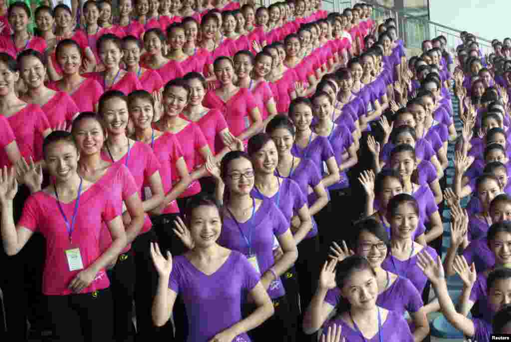 Volunteers, who will be hostesses of Nanjing 2014 Youth Olympic Games, smile and wave during training in Nanjing, Jiangsu province, July 13, 2014. The eastern Chinese city will host the 2014 Youth Olympic Games between August 16-28.