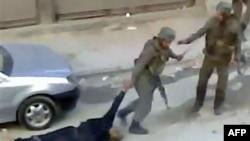 Hình ảnh từ video nghiệp dư cho thấy binh sĩ đang lôi 1 thi thể ở Damascus, Syria, 10/11/2011