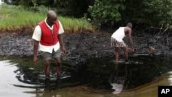 FILE - Men walk in an oil slick covering a creek near Bodo City in the oil-rich Niger Delta region of Nigeria, June 10, 2010.