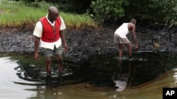 FILE - Men walk in an oil slick covering a creek near Bodo City in the oil-rich Niger Delta region of Nigeria, June 10, 2010.