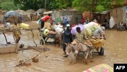Des habitants de Niamey, capitale du Niger, évacuent leurs maisons inondées, le 19 août 2012. (AFP PHOTO / BOUREIMA HAMA)