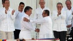El presidente colombiano Juan Manuel Santos y el ex comandante guerrillero, Rodrigo Londoño, se estrechan las manos durante el acto de firma de la paz en Cartagena.