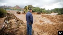 Seorang pria menatap jalan berlumpur akibat banjir bandang di Colorado City, Arizona, sementara petugas berusaha membersihkan kota (15/9).