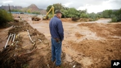 Following a flash flood that killed at least 15 people, a man looks on as crews clear mud and debris from a road in Colorado City, Ariz., which adjoins Hildale, Utah, Sept. 15, 2015.