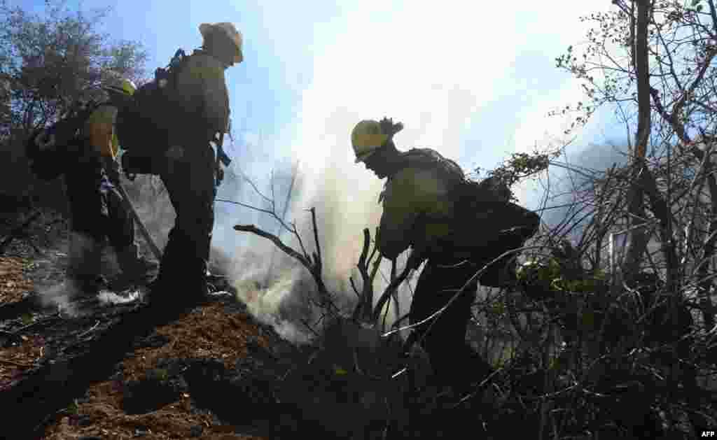 Los bomberos tratan de verificar y controlar las áreas donde ya lograron avances contra las llamas, cerca de Banning, California.