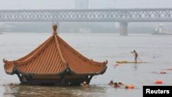 在被洪水淹没的武汉长江旁的一个只露出顶部的亭子边有武汉民众在游泳。(2020年7月8日)