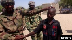FILE - A Chadian soldier embraces a former child soldier of insurgent group Boko Haram in Ngouboua, Chad, April 22, 2015. An 11-year-old boy arrested by soldiers says Boko Haram trained him as a suicide bomber and his mission was to blow himself up among refugees in a northeast Nigerian camp.