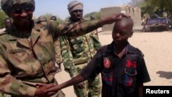 A Chadian soldier embraces a former child soldier of insurgent group Boko Haram in Ngouboua, Chad, April 22, 2015. The young men said they were Chadian nationals forced to join Boko Haram while studying the Quran in Nigeria, and that they escaped and turned themselves in to Chadian authorities. (REUTERS/Moumine Ngarmbassa)