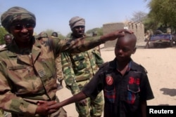 FILE - A Chadian soldier embraces a former child soldier of insurgent group Boko Haram in Ngouboua, Chad, April 22, 2015. The young men said they were Chadian nationals forced to join Boko Haram while studying the Quran in Nigeria, and that they escaped and turned themselves in to Chadian authorities.