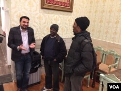 Kazi Mannan speaks with two of his regular homeless guests at his restaurant, which welcomes paying and non-paying customers. (J. Taboh/VOA)